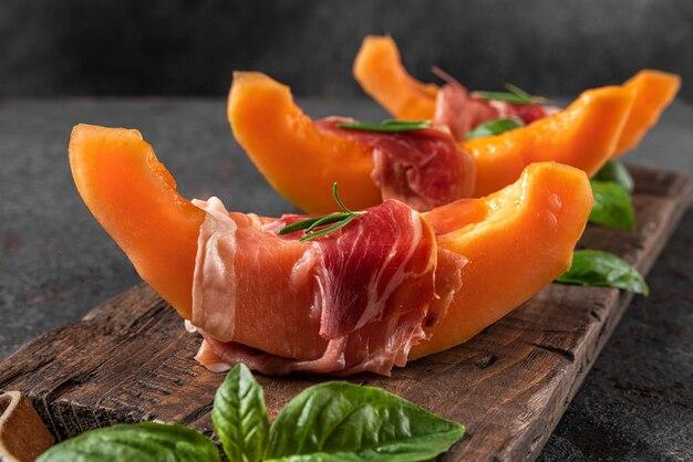 Verse meloen meloen met prosciutto ham en basilicum op zwarte achtergrond. italiaans eten voorgerecht. detailopname