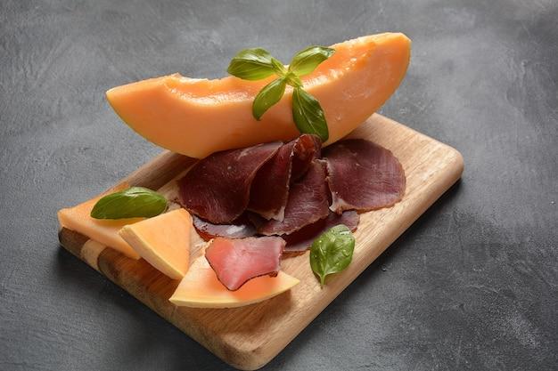 Verse meloen met ham op een houten snijplank