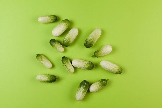Verse minikomkommers van het ras piccolo bianco op een mooie groene tafel. uitzicht van boven.
