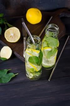 Verse mojito-drankjes in flessen en ingrediënten - citroen en munt