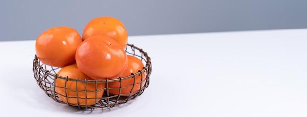 Verse mooie gesneden zoete persimmon kaki geïsoleerd op een witte keukentafel met grijze blauwe achtergrond, chinees nieuwe maanjaar ontwerpconcept, close-up.