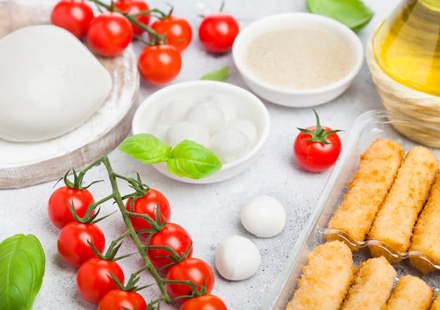 Verse mozzarella kaas op vintage snijplank met tomaten en basilicum blad met olijfolie en lade met kaas stokken op stenen keuken.