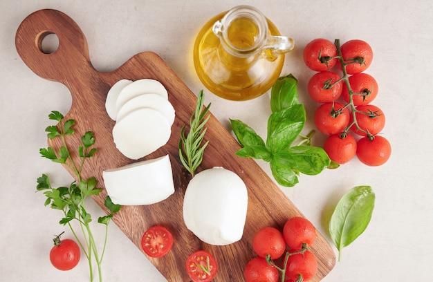 Verse mozzarellakaas, zachte italiaanse kazen, tomaat en basilicum, olijvenolie en rozemarijn op houten dienende raad over lichte houten oppervlakte. gezond eten. bovenaanzicht. plat leggen.
