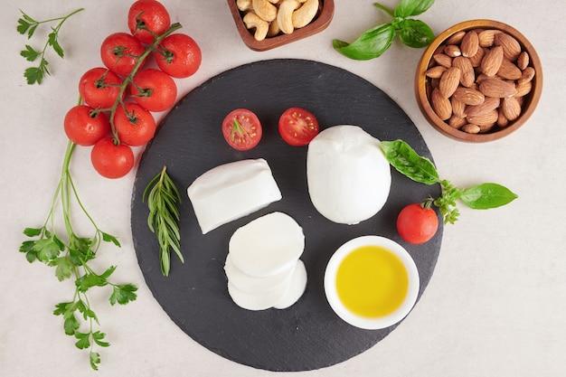Verse mozzarellakaas, zachte italiaanse kazen, tomaat en basilicum, olijvenolie en rozemarijn op houten dienende raad over lichte oppervlakte. gezond eten. bovenaanzicht. plat leggen.