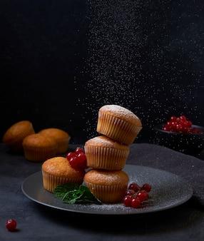 Verse muffins toren met bessen in plaat op zwarte achtergrond