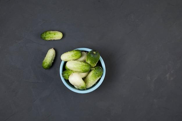 Verse multi-coloured minikomkommers in een blauwe kom op een donkergrijze tafel. organische groenten. ongewone variëteit aan komkommers. kopieer ruimte.