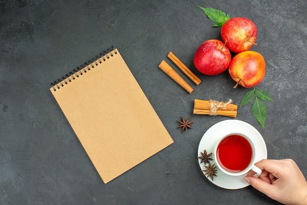 Verse natuurlijke biologische rode appels met groene bladeren, kaneellimoenen en een kopje thee naast een notitieboekje op zwarte achtergrond