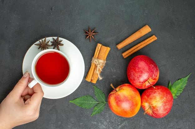 Verse natuurlijke biologische rode appels met groene bladeren, kaneellimoenen en een kopje thee op zwarte achtergrond
