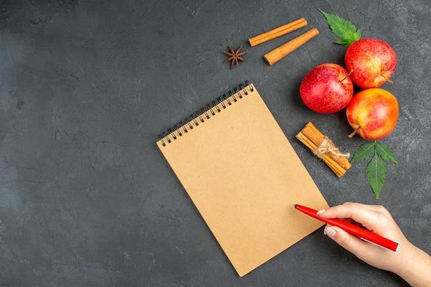 Verse natuurlijke biologische rode appels met groene bladeren, kaneellimoenen naast notitieboekje met pen op zwarte achtergrond