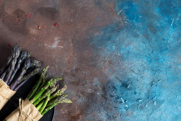 Verse natuurlijke biologische twee bundels van groene en paarse aspergegroenten op donkere steen.