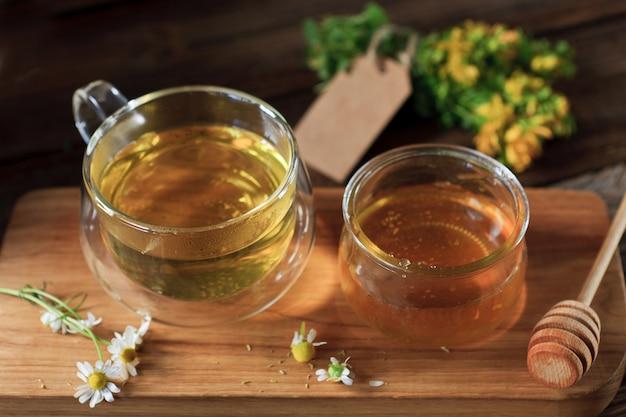 Verse natuurlijke honing in een glazen pot en kruidenthee in een glazen mok op een houten bord. close-up, selectieve aandacht, ondiepe scherptediepte