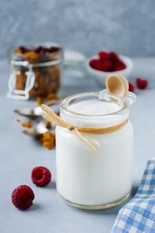 Verse natuurlijke yoghurt in een glazen pot op grijze betonnen of stenen tafel. gezond eten voor het ontbijt. melk zuivelproduct. selectieve aandacht.