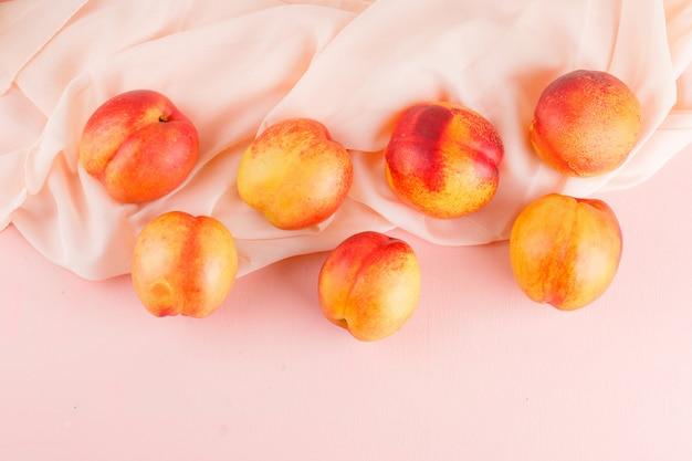 Verse nectarines op roze en textiel oppervlak. plat lag.