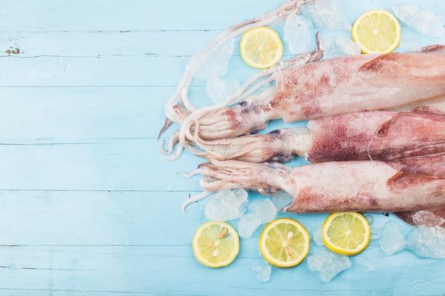 Verse octopus of inktvis rauw op houten bord met ingrediënten