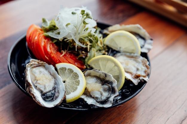 Verse oesters close-up op zwarte plaat, geserveerd tafel met oesters, citroen, ijs en salade.
