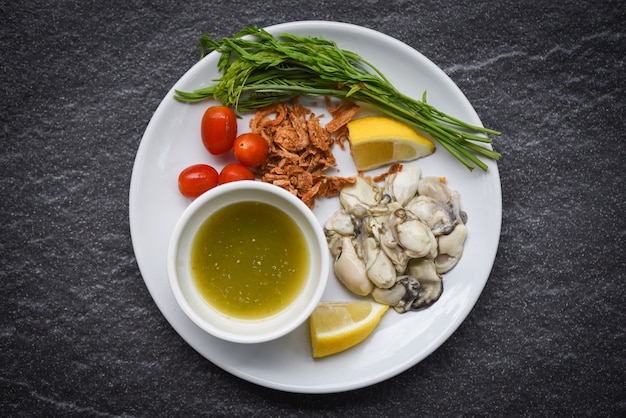 Verse oesters geserveerd op plaat en donkere ondergrond oestersalade met plantaardige tomaat citroen en kruid zeevruchten saus