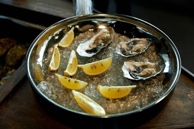 Verse oesters in ijs met citroen op een rond ijzeren dienblad