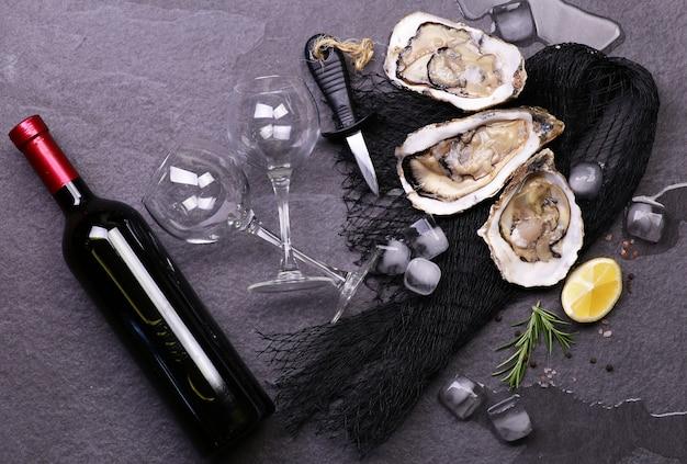 Verse oesters met een fles wijn op een zwarte stenen ondergrond