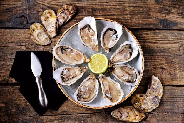 Verse oesters met plakjes citroen op ijs op oude houten achtergrond