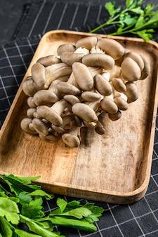 Verse oesterzwammen in een houten kom met peterselie. biologisch voedsel. zwarte achtergrond. bovenaanzicht