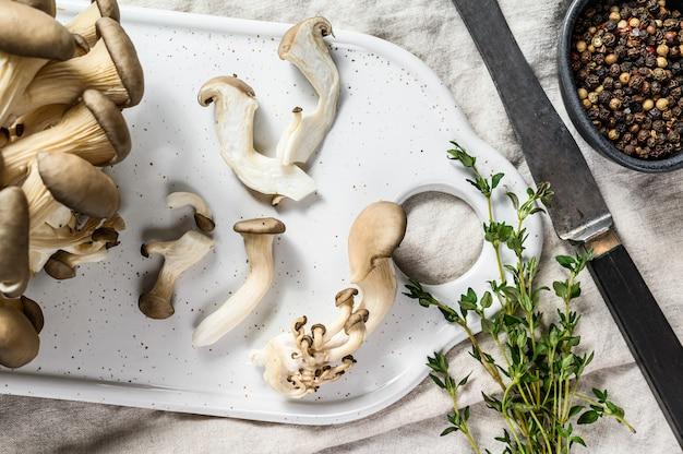 Verse oesterzwammen op een wit hakbord met tijm. grijze achtergrond. bovenaanzicht