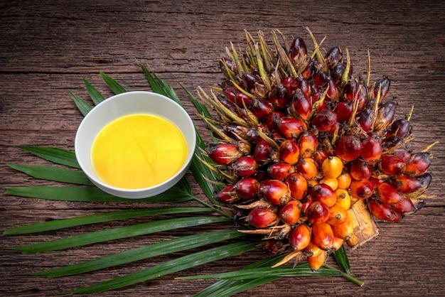 Verse oliepalm en palmolie op houten oppervlak