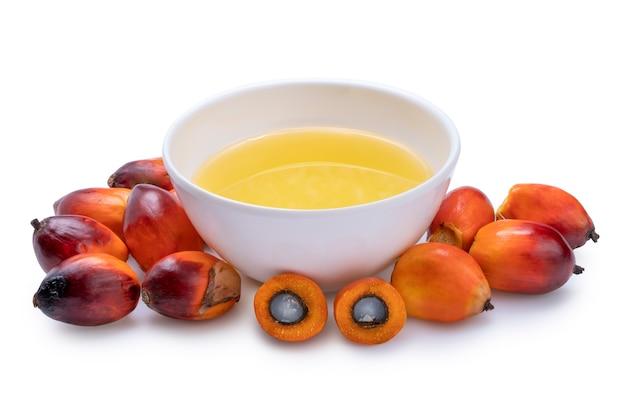 Verse oliepalmvruchten en kokende palmolie die op de witte ruimte wordt geïsoleerd.