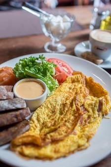 Verse omelet geserveerd met groene salade, tomaten. sause en breab - close-up bekijken. kopje koffie op een achtergrond. traditioneel ontbijt. gezond eten.