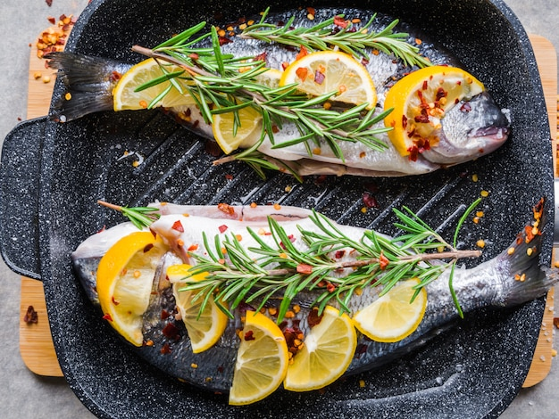 Verse ongekookte dorado of zeebrasem vis met plakjes citroen, specerijen, kruiden en rozemarijn op de donkere koekenpan .. mediterrane keuken. bovenaanzicht gezond en dieet voedsel concept.