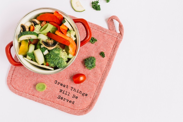 Verse ongekookte groenten in het koken van pot op placemat tegen witte achtergrond