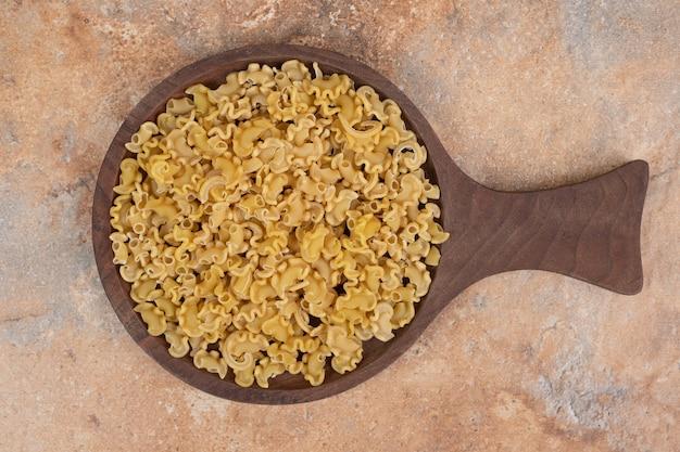 Verse ongekookte macaroni op houten bord op marmeren achtergrond
