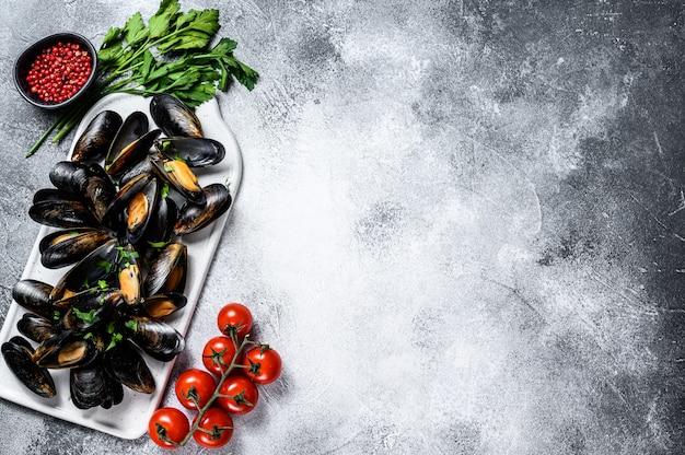 Verse ongekookte mosselen in schelpen. het concept van koken in tomatensaus met peterselie. grijze achtergrond. bovenaanzicht. ruimte voor tekst