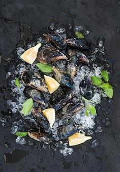 Verse ongekookte mosselen met citroen, kruiden en specerijen op afgebroken ijs over donkere leisteen stenen muur