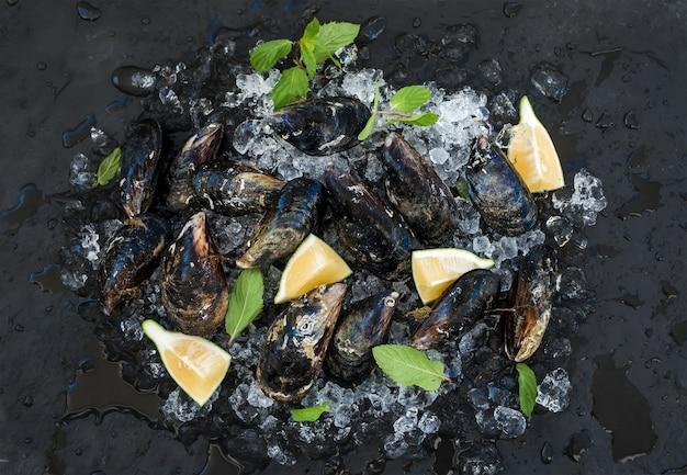 Verse ongekookte mosselen met citroen, kruiden en specerijen op afgestoken ijs over donkere leisteen