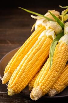 Verse oogst van maïs, biologische maïskolf met bladeren op donkere houten achtergrond