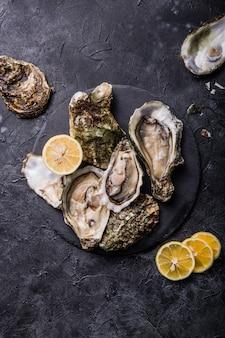 Verse open oesters. gezonde zeevruchten. diner in restaurant. gourmet eten. donker oppervlak