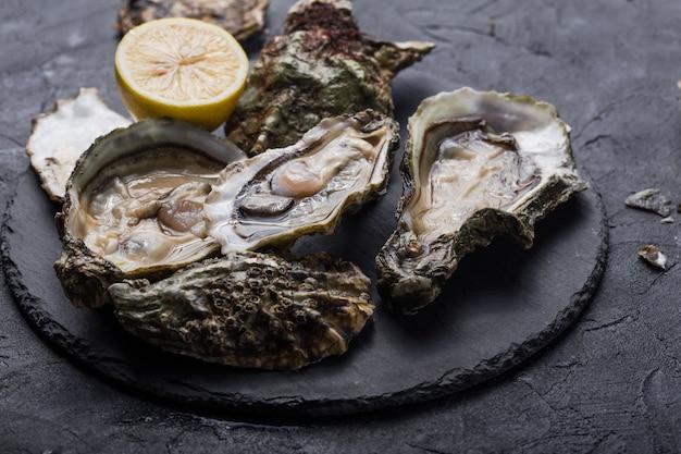 Verse open oesters met poot van een zwarte kat. gezonde zeevruchten. diner in restaurant. gourmet eten. donker oppervlak