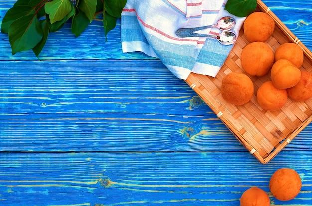 Verse oranje abrikozen in een rieten dienblad op een blauwe houten achtergrond en een half met een bot.