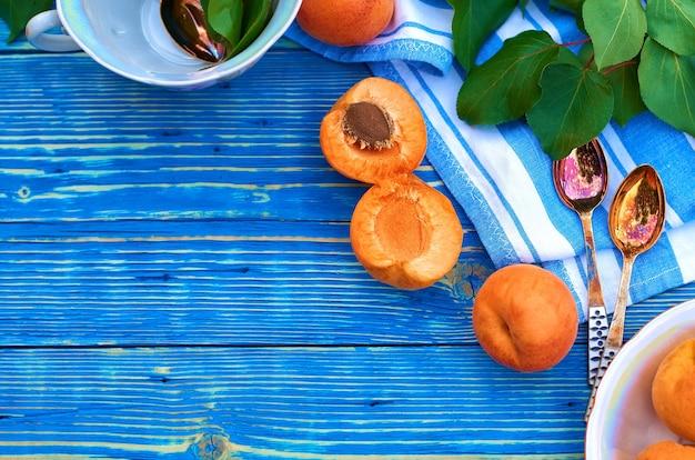 Verse oranje abrikozen op een blauwe houten achtergrond en een half met een steen. servet, lepels en groene bladeren.