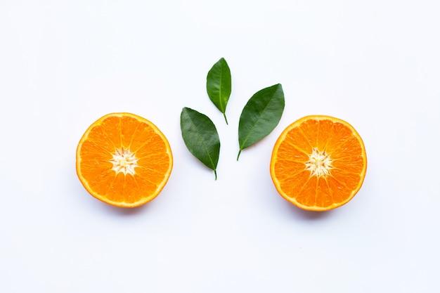 Verse oranje citrusvruchten met bladeren op witte achtergrond.