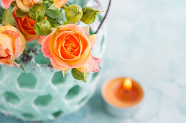 Verse oranje rozenbloemen in muntvaas en aangestoken kaars