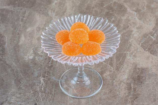 Verse oranje snoepjes op glazen servies over grijs oppervlak.