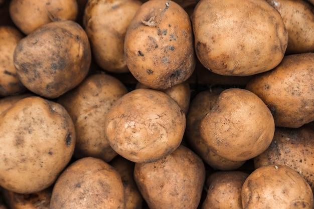 Verse organische aardappels op tribune op supermarktachtergrond