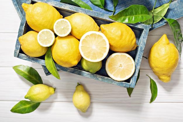 Verse organische citroenvruchten met bladeren op houten lijst