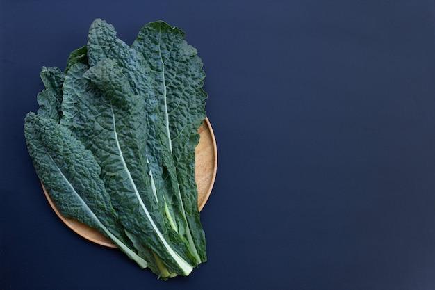 Verse organische groene boerenkoolbladeren op donker.
