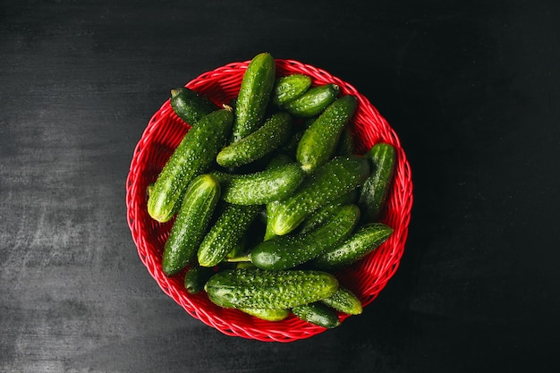 Verse organische komkommers in rode mand op witte houten tafel met groene en rode en chilipepers, venkel, zout, zwarte peperkorrels, knoflook, erwt, close-up, gezond concept, bovenaanzicht, plat leggen