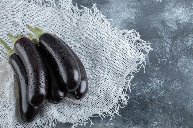 Verse organische paarse aubergines op grijze achtergrond.