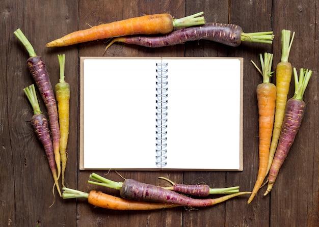 Verse organische regenboogwortelen met receptenboek op een houten mening van de lijstbovenkant