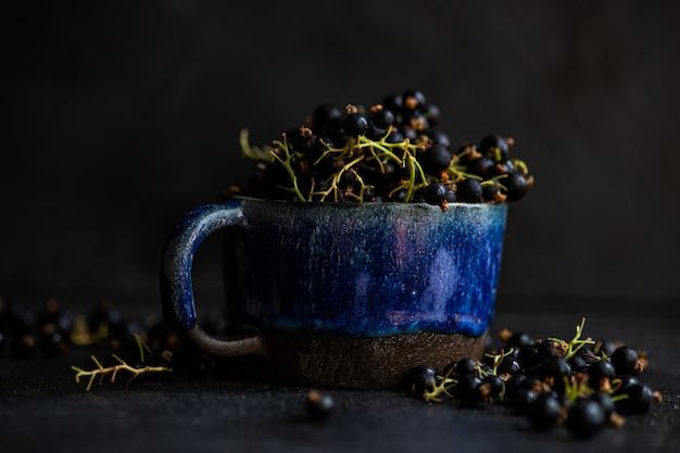 Verse organische zwarte bessenbessen in een ceramische kom op donker met exemplaarruimte
