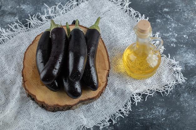 Verse paarse aubergine op een houten bord en een fles olie. bovenaanzicht.